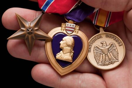 Man Holding Purple Heart, Bronze and National Defense War Medals in The Palm of His Hand. photo