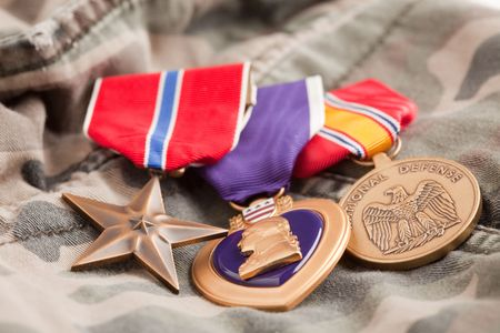valor: Bronze, Purple Heart and National Defense Medals on Camouflage Material.