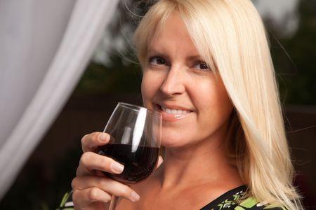 social gathering: Beautiful blonde smiling woman at an evening social gathering tasting wine.