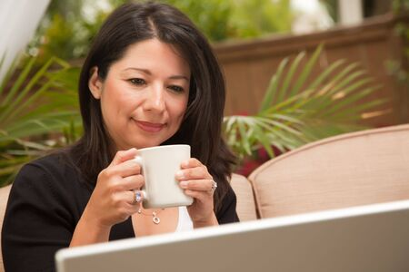 Hispanic Woman with Coffee and Laptop On Her Patio. photo