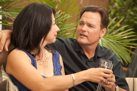 Attractive Hispanic and Caucasian Couple Drinking Wine Outside. photo