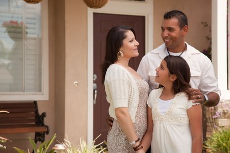 Small Hispanic Mother, Father and Daughter in Front of Their Home. photo