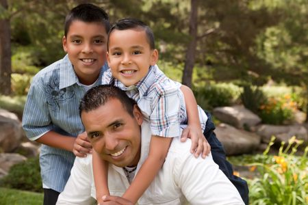 latino family: Father and Sons Portrait in the Park.