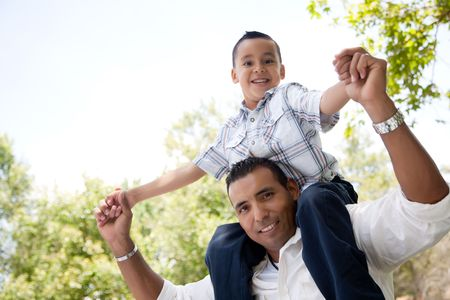 preadolescent: Hispanic Father and Son Having Fun Together in the Park Stock Photo