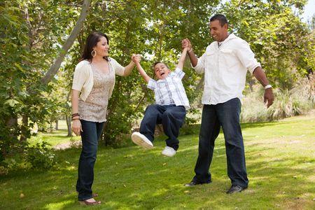 Hispanic Man, Woman and Child having fun in the park. Stock Photo