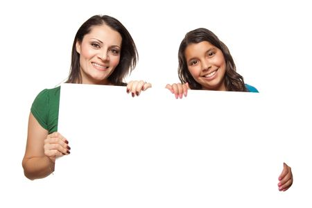 Pretty Hispanic Girl and Mother Holding Blank Board Isolated on a White Background. photo