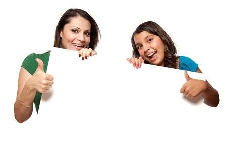 latino: Pretty Hispanic Girl and Mother Holding Blank Board Isolated on a White Background.