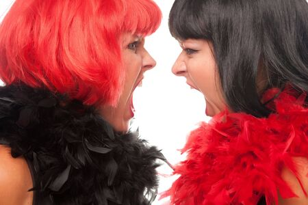 Red and Black Haired Women with Boas Screaming at Each Other on a White Background.
