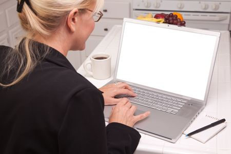 여자 빈 화면으로 노트북을 사용하는 부엌에 앉아.