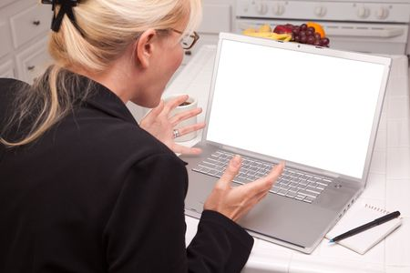 Woman Sitting In Kitchen Using Laptop with Blank Screen photo