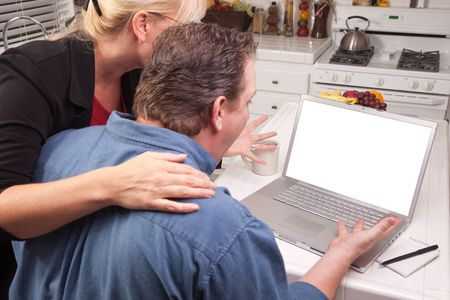Couple In Kitchen Using Laptop with Blank Screen. Screen can be easily used for your own message or picture. photo