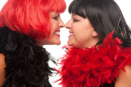 boas: Red and Black Haired Women with Feather Boas Touching Noses and Smiling at Each Other. Stock Photo