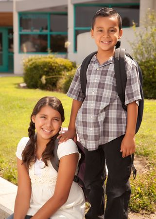 sibling: Cute Hispanic Brother and Sister Wearing Backpacks Ready for School.