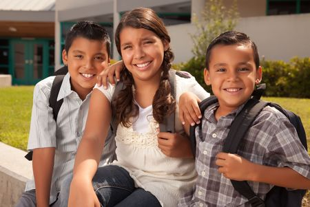 latino: Cute Brothers and Sister Wearing Backpacks Ready for School.