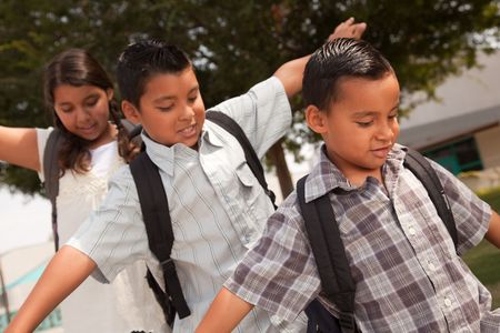 Cute Brothers and Sister with Backpacks Having Fun Walking to School. photo