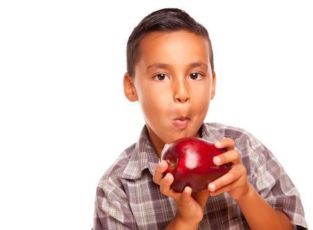 hispanic boy: Hispanic adorable Chico Comer una manzana roja grande aislados sobre fondo blanco.