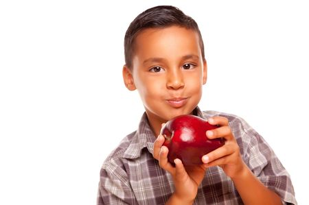 Adorable Hispanic Boy Eating a Large Red Apple Isolated on a White Background. photo