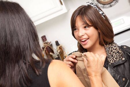 Hispanic Mom in the Kitchen Hands Lunch to Her Pretty Schoolgirl. photo
