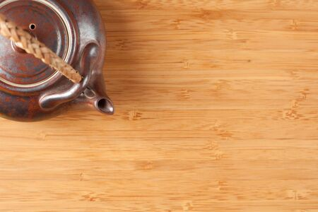 Tea Pot and Bamboo Textured Surface Background with Plenty of Room for Text. Focus is on the Tea Pot. photo