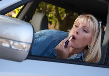 Attractive Woman Putting on Lipstick While Driving. photo