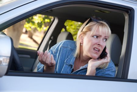 Concerned Blonde Woman Using Cell Phone While Driving. photo