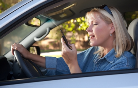 sms text: Attractive Blonde Woman Text Messaging on Her Cell Phone While Driving.
