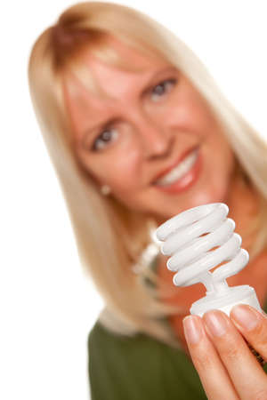 Attractive Blonde Woman Holds Energy Saving Light Bulb Isolated on a White Background with Narrow Depth of Field. photo