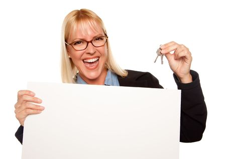 Attractive Blonde Holding Keys and Blank White Sign Isolated on a White Background. photo
