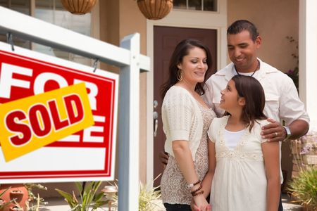 real estate sold: Hispanic Mother, Father and Daughter in Front of Their New Home with Sold Home For Sale Real Estate Sign.