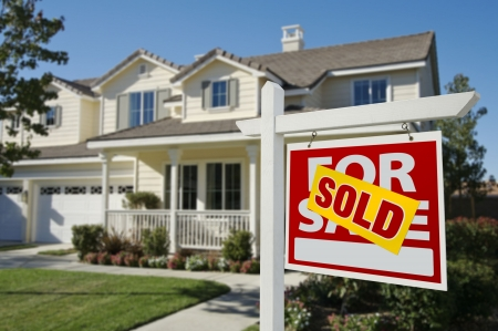 Sold Home For Sale Sign in Front of Beautiful New House. photo