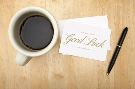 Good Luck Note Card, Pen and Coffee Cup on Wood Background.