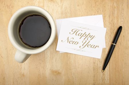 Happy New Year Note Card, Pen and Coffee Cup on Wood Background photo