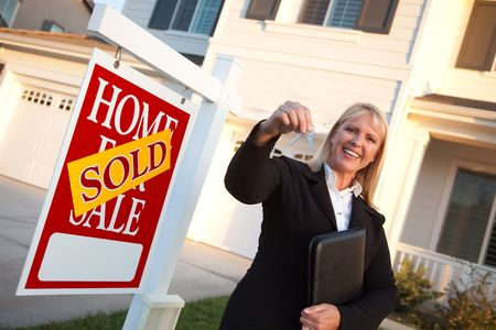 sales lady: Female Real Estate Agent Handing Over the House Keys in Front of a Beautiful New Home and Real Estate Sign.