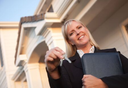 real estate sold: Female Real Estate Agent Handing Over Keys in Front of Beautiful House.