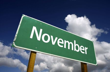 months: November Green Road Sign with dramatic blue sky and clouds - Months of the Year Series.