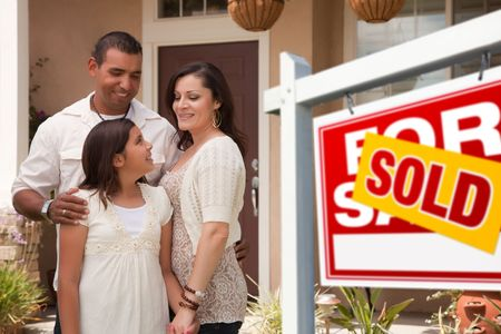 latino: Hispanic Mother, Father and Daughter in Front of Their New Home with Sold Home For Sale Real Estate Sign.