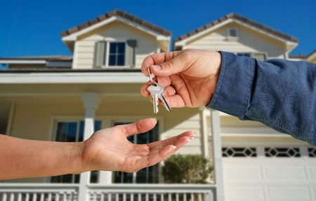 purchasing: Handing Over the House Keys in Front of a Beautiful New Home.