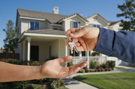 Handing Over the House Keys in Front of a Beautiful New Home. photo