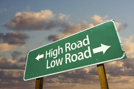 certain: High and Low Road Green Road Sign with dramatic blue sky and clouds. Stock Photo
