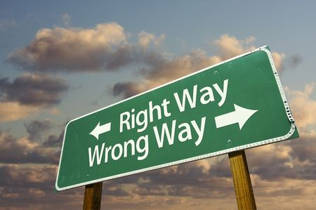 wrong way: Right and Wrong Way Green Road Sign with dramatic blue sky and clouds. Stock Photo