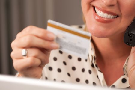 Beautiful Woman on the Phone Holding Her Credit Card. photo