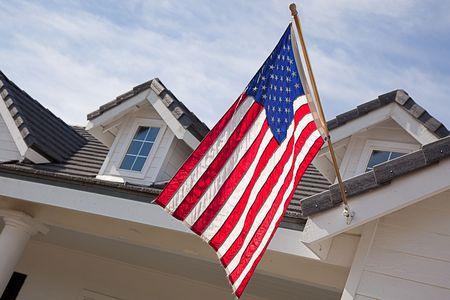 banderas america: Abstracta House Facade & American Flag contra un cielo azul  Foto de archivo