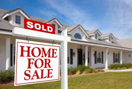 home for sale: Venduto Home For Sale Sign davanti a Beautiful New Home.