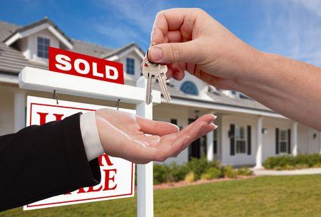 real estate sold: Entrega en las llaves de casa en frente del Home vendi� de nuevo contra un cielo azul