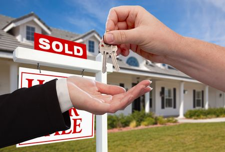 real estate sold: Handing Over the House Keys in Front of Sold New Home Against a Blue Sky