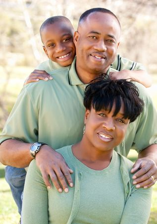 two generation family: Attractive African American Man, Woman and Child posing in the park.