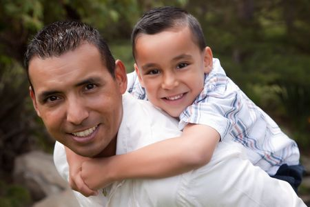 kinship: Hispanic Father and Son Having Fun Together in the Park Stock Photo