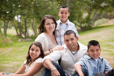 single family home: Happy Hispanic Family Portrait In the Park.
