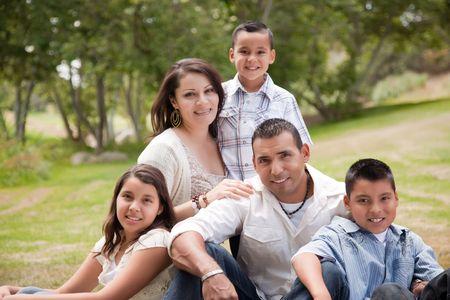 familia unida: Retrato de familia hispana feliz en el parque.