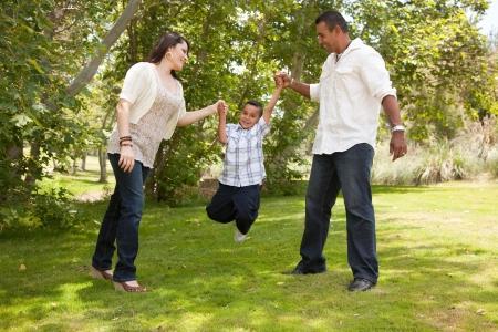 latino family: Hispanic Man, Woman and Child having fun in the park. Stock Photo